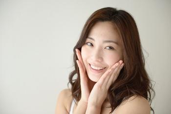 笑顔で頬に手を当てる女性.jpg